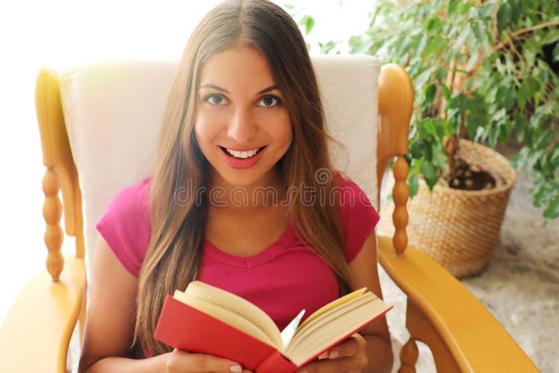 Jovem mulher em casa que senta-se na cadeira confortável que relaxa em seu livro de leitura da sala de visitas Olha a c?mera fotografia de stock