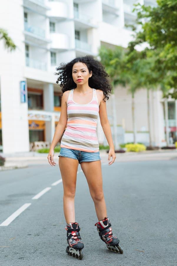 Jovem mulher em patins de rolo imagem de stock