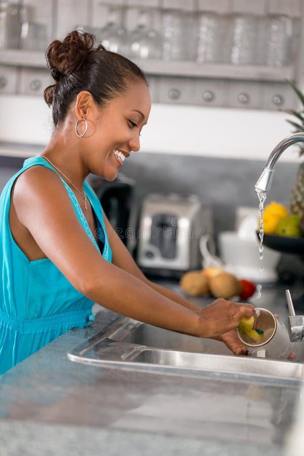 Jovem mulher em pratos de lavagem da cozinha imagens de stock royalty free