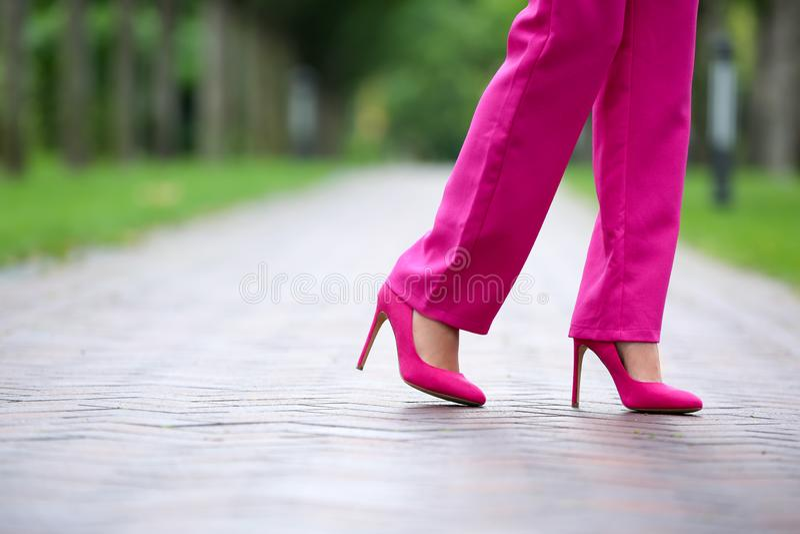 Jovem mulher em sapatas alto-colocadas saltos à moda que anda fora fotografia de stock royalty free