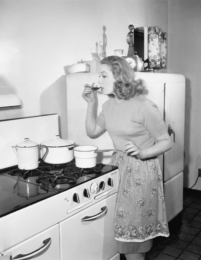 Jovem mulher em um avental em sua cozinha que prova seu alimento de um potenciômetro (todas as pessoas descritas não são nenhum d imagem de stock