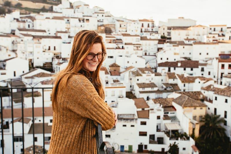 A jovem mulher em um balcão está olhando uma vila branca mediterrânea imagem de stock