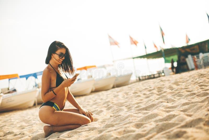 Jovem mulher em um biquini na praia usando um telefone celular imagens de stock royalty free