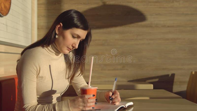 A jovem mulher em um café faz anotações em um caderno e bebe o suco fotos de stock royalty free