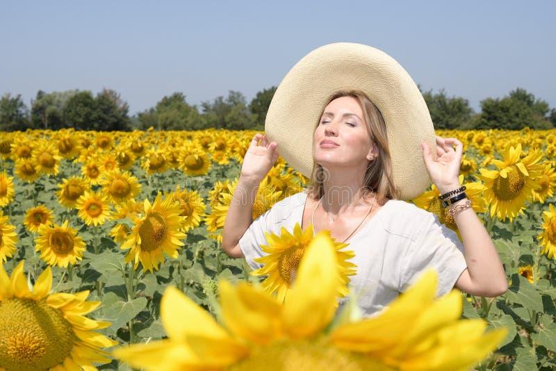 A jovem mulher em um campo do girassol com um chapéu desproporcionado toma toma sol e uma respiração profunda fotografia de stock royalty free