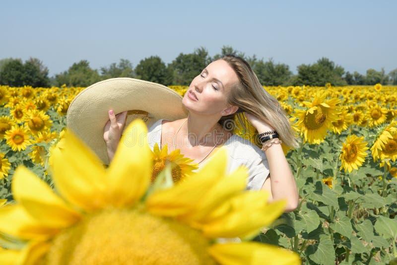 A jovem mulher em um campo do girassol com um chapéu em sua mão toma toma sol quando refrescar levantando o cabelo imagem de stock royalty free