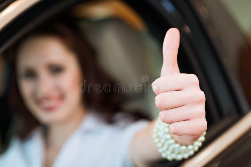Jovem mulher em um carro e em mostrar polegares acima fotografia de stock