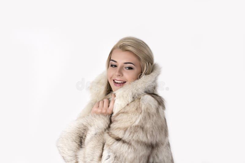 A jovem mulher em um casaco de pele está no parque coberto de neve Sh imagens de stock royalty free