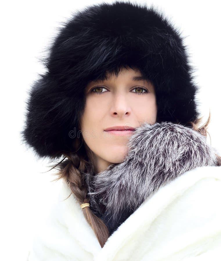Jovem mulher em um chapéu forrado a pele preto fotografia de stock royalty free