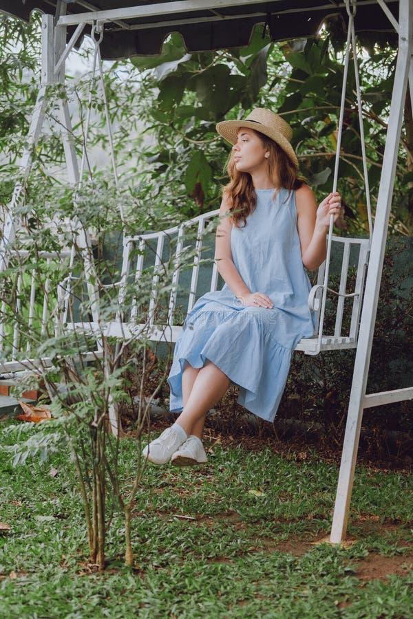 A jovem mulher em um chapéu senta-se em um balanço branco imagens de stock royalty free