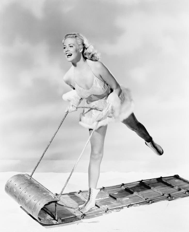 Jovem mulher em um equipamento patinando no gelo no trenó (todas as pessoas descritas não são umas vivas mais longo e nenhuma pro fotos de stock royalty free