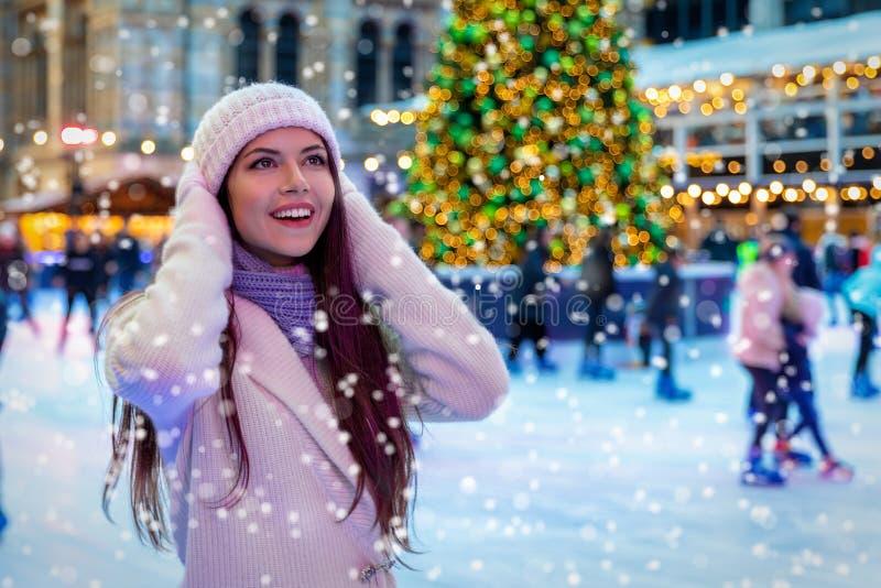 A jovem mulher em um mercado do Natal aprecia a neve de queda imagem de stock