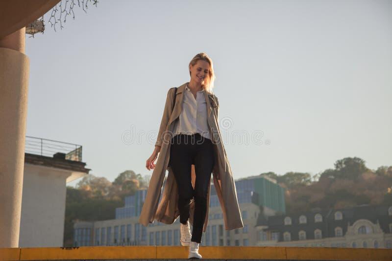 Jovem mulher em um revestimento à moda da mola em vidros elegantes em um t-shirt branco em uma bolsa de couro preta que anda avan imagem de stock royalty free