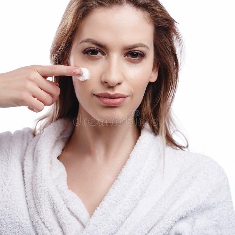 Jovem mulher em um roupão que aplica um creme em seus cara, termas e retrato do cuidado, cara natural limpa, retrato em um fundo  imagem de stock royalty free