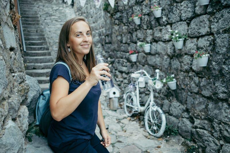 A jovem mulher em um t-shirt azul bebe a água da garrafa plástica o fotografia de stock royalty free