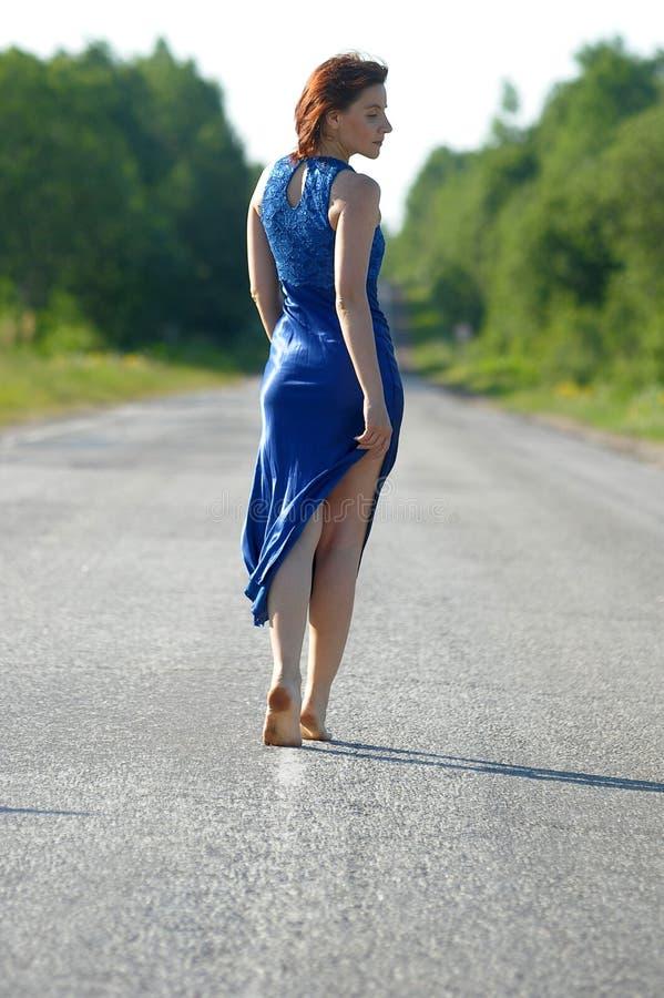 Jovem mulher em um vestido azul na estrada imagens de stock royalty free