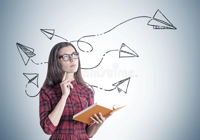 Jovem mulher em um vestido com um livro, planos de papel foto de stock