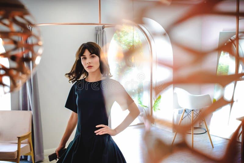 jovem mulher em um vestido preto elegante com um telefone em sua mão, em uma sala com um interior cor-de-rosa imagem de stock royalty free