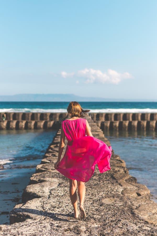 Jovem mulher em um vestido vermelho longo e com um vidro do vinho que levanta no fundo do mar foto de stock royalty free