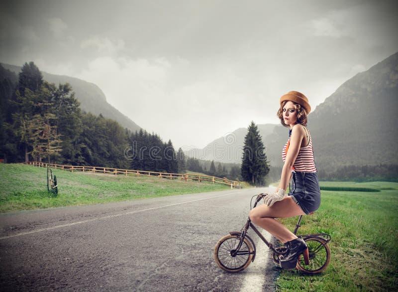Jovem mulher em uma bicicleta pequena fotos de stock