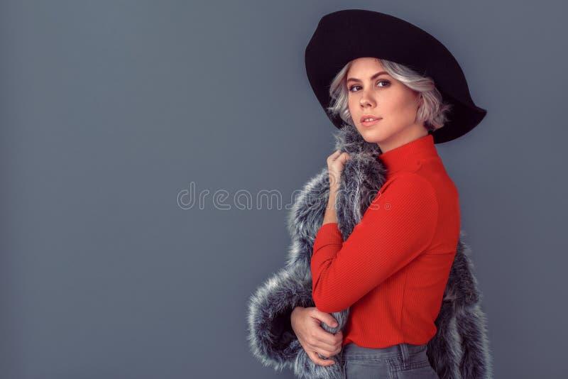 Jovem mulher em uma blusa e em um casaco de pele vermelhos isolados na tomada cinzenta da parede do revestimento imagens de stock royalty free