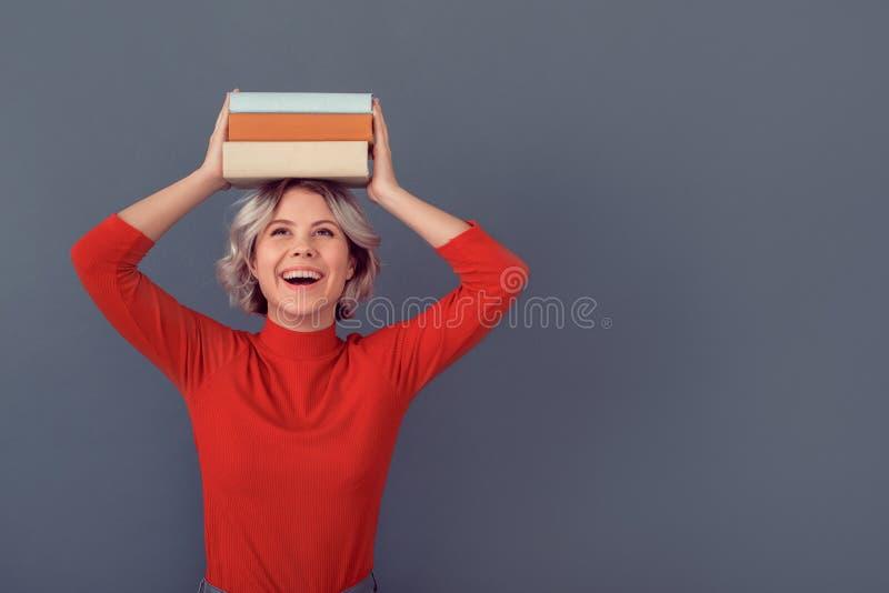 Jovem mulher em uma blusa vermelha isolada na pilha cinzenta da parede dos livros fotos de stock