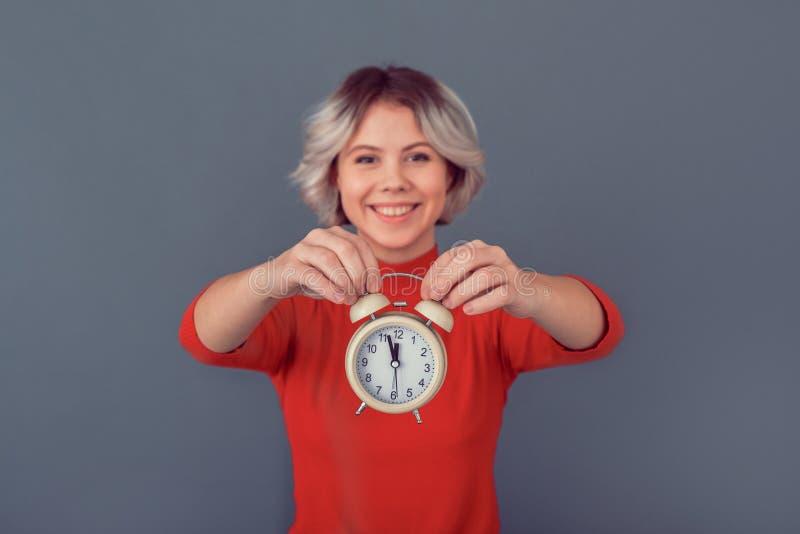 Jovem mulher em uma blusa vermelha isolada no tempo cinzento da parede trabalhar foto de stock
