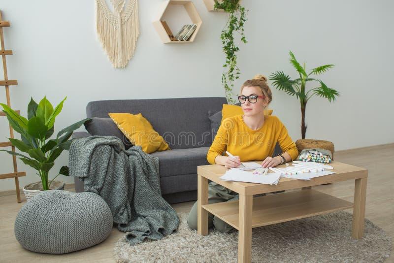 A jovem mulher em uma camiseta amarela tira e pensando na sala imagem de stock royalty free