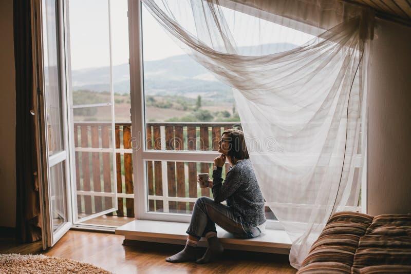 Jovem mulher em uma camiseta e nas calças de brim do noivo que relaxam perto da janela grande foto de stock