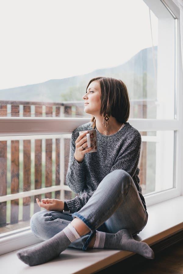 Jovem mulher em uma camiseta e nas calças de brim do noivo que relaxam perto da janela grande fotografia de stock royalty free
