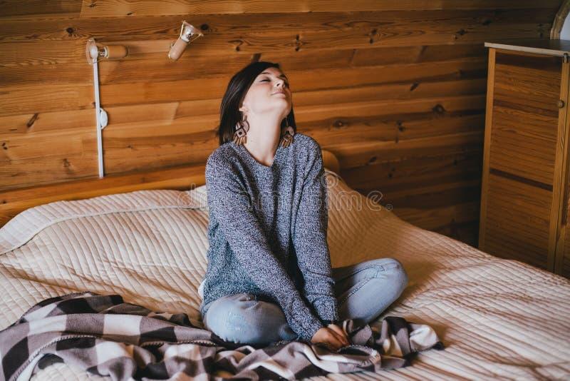 Jovem mulher em uma camiseta feita malha que relaxa em uma cama foto de stock
