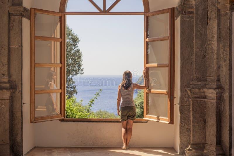 Jovem mulher em uma grande janela aberta imagens de stock