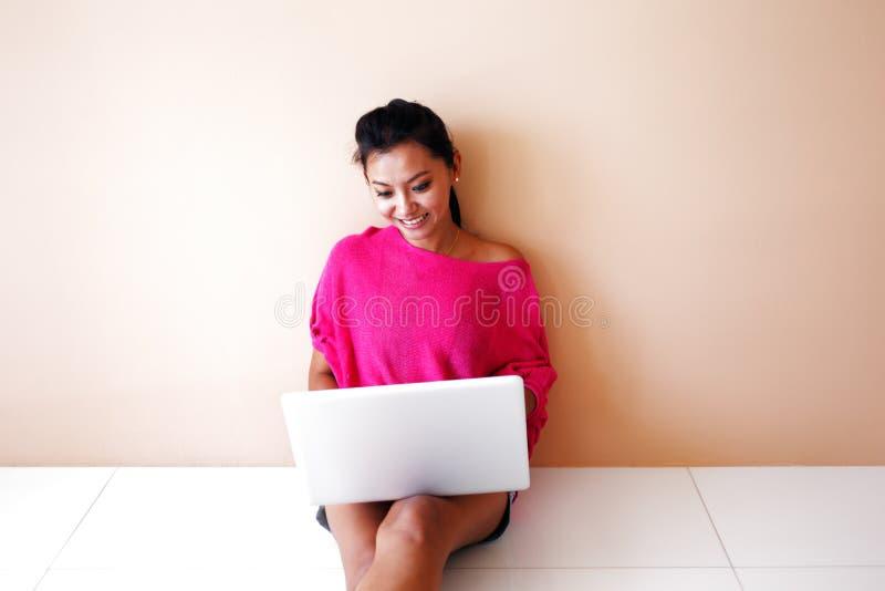 Jovem mulher em uma parte superior cor-de-rosa usando um portátil imagens de stock