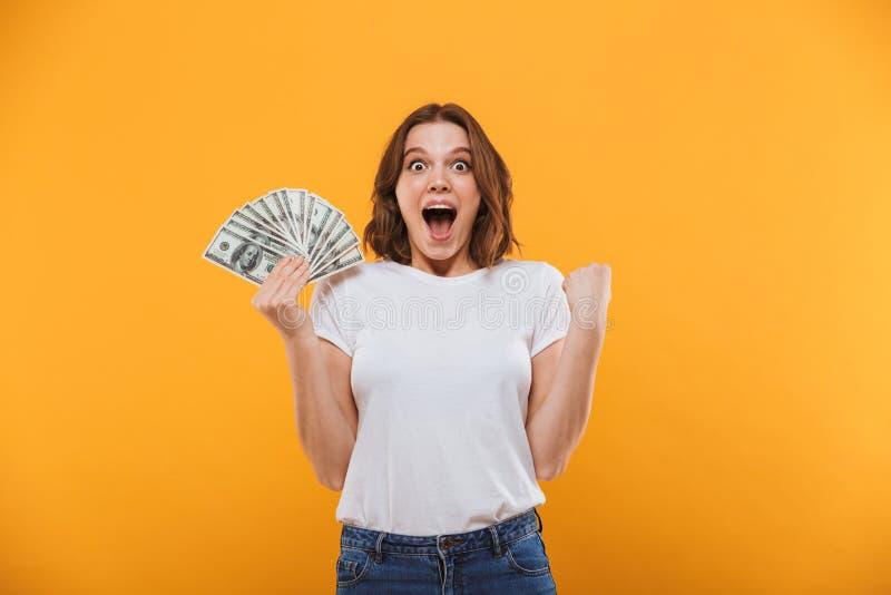 A jovem mulher emocional que guarda o dinheiro faz o gesto do vencedor fotos de stock royalty free