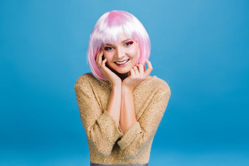 Jovem mulher encantador alegre com composição cor-de-rosa brightful dos ouropéis que sorri à câmera no fundo azul Tempo feliz, co fotos de stock royalty free