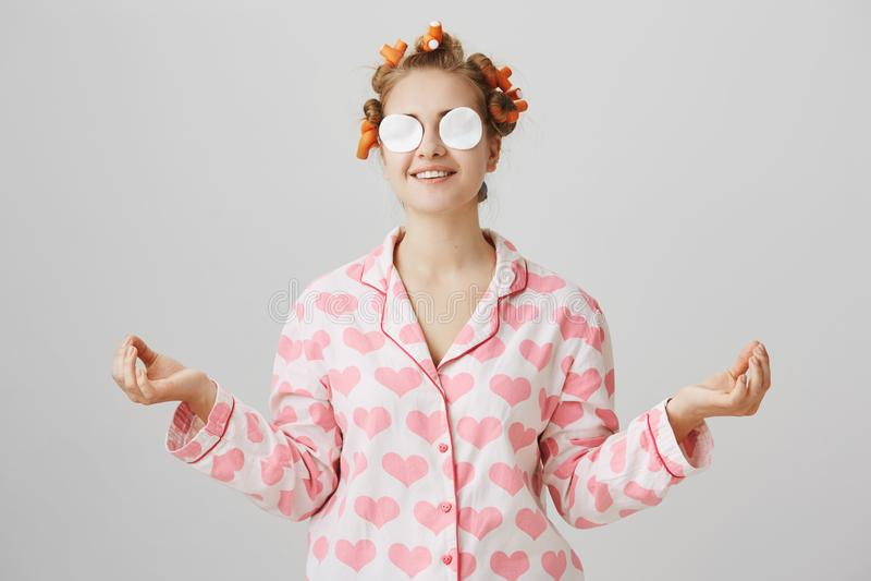 Jovem mulher encantador brincalhão engraçada com cabelo-encrespadores e almofadas de algodão nos olhos, sorrindo happilly ao esta fotos de stock