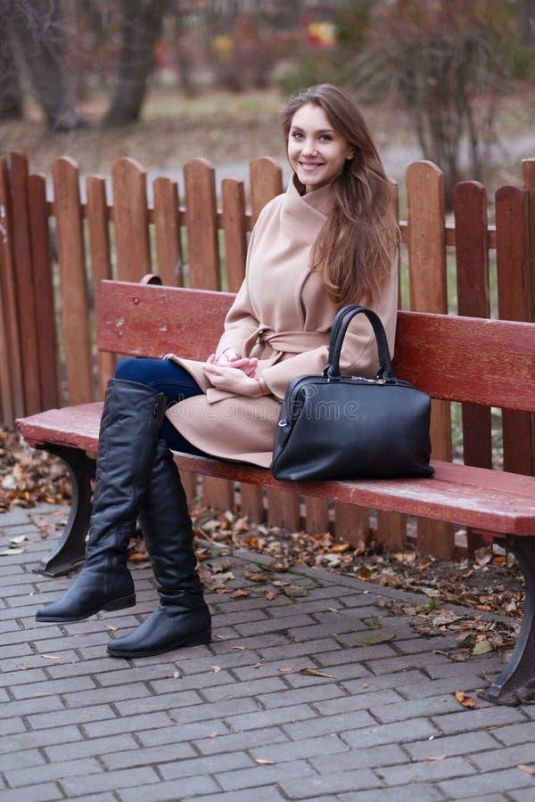 Jovem mulher encantador com cabelo marrom longo em um revestimento bege imagens de stock royalty free