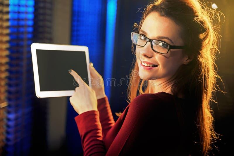 Jovem mulher encantador que aponta uma tabuleta foto de stock royalty free