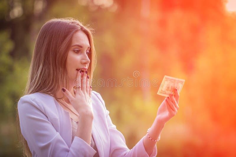 Jovem mulher encaracolado entusiasmado que guarda o dinheiro imagem de stock royalty free