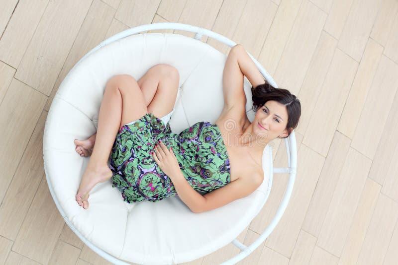 A jovem mulher encontra-se na espreguiçadeira do círculo foto de stock royalty free