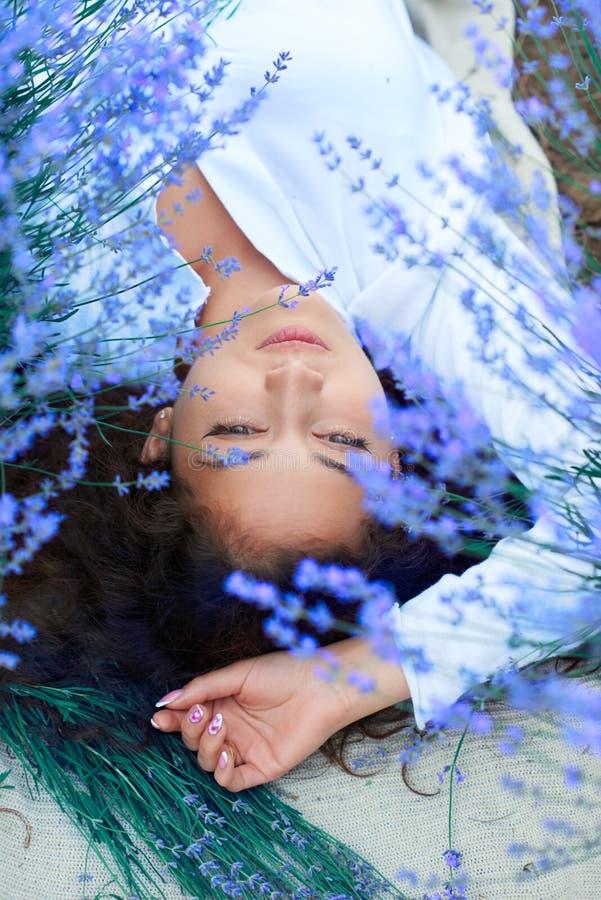A jovem mulher encontra-se no campo de flor da alfazema, paisagem bonita do ver?o foto de stock