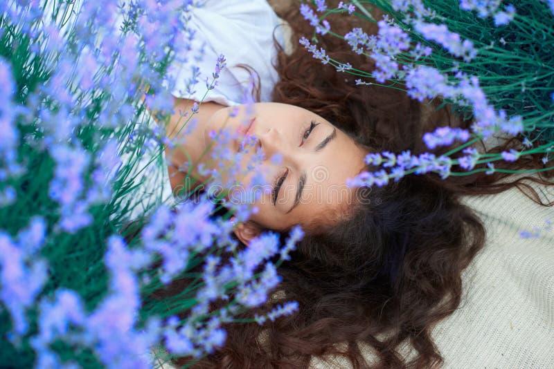 A jovem mulher encontra-se no campo de flor da alfazema, paisagem bonita do ver?o fotos de stock royalty free