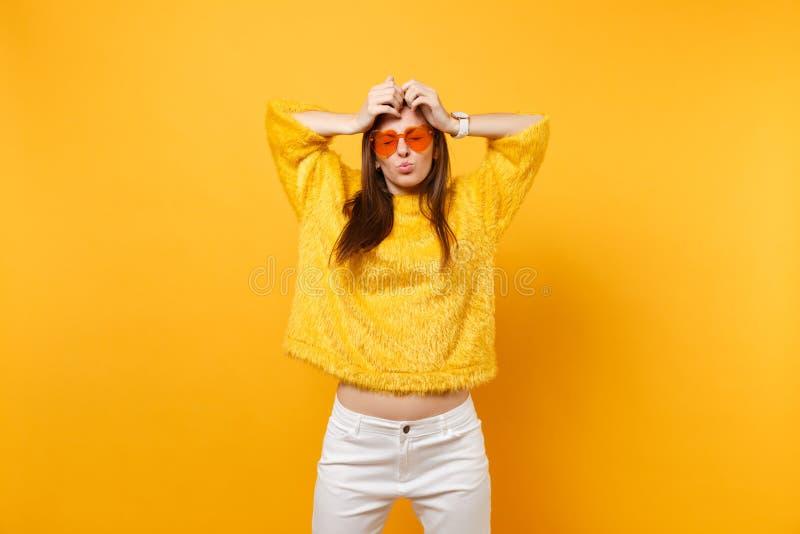 A jovem mulher engraçada em vidros alaranjados do coração da camiseta da pele engana em torno dos bordos de sopro que põem as mão fotos de stock