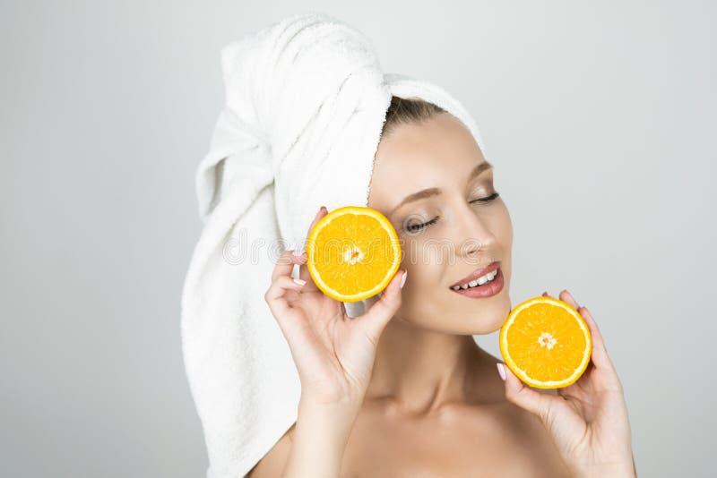 Jovem mulher engraçada na toalha branca em sua cabeça que guarda uma laranja perto de sua cara e de um outro queixo próximo branc foto de stock