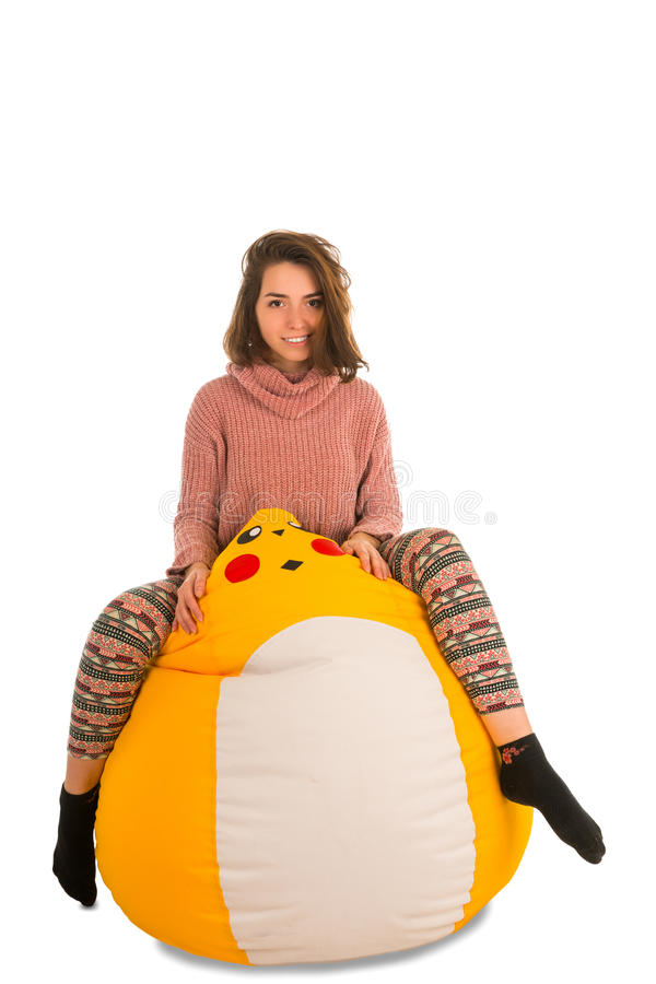 Jovem mulher engraçada que senta-se na cadeira amarela do beanbag isolada no wh imagem de stock