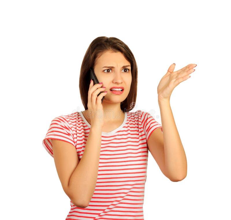 A jovem mulher entendendo mal e distante da chamada que fala no telefone celular tem muitas perguntas menina emocional isolada no imagem de stock royalty free