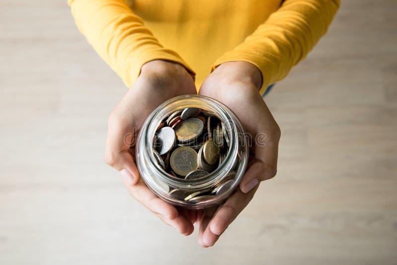 A jovem mulher entrega guardar o frasco de vidro com as multi moedas da moeda para dentro fotografia de stock