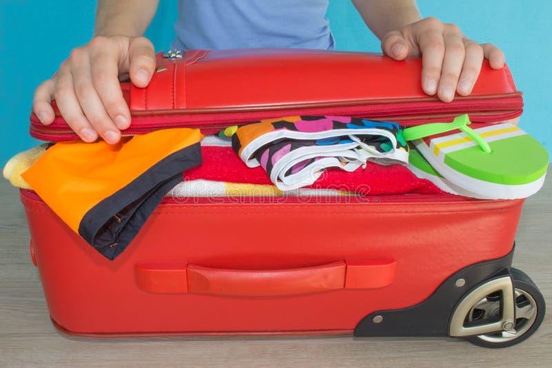 A jovem mulher entrega a mala de viagem da embalagem Women& x27; a roupa e os acessórios de s em coisas vermelhas da mala de viag foto de stock royalty free