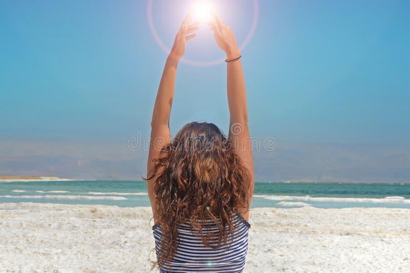 A jovem mulher entrega o travamento da energia do sol a menina de cabelos compridos senta-se na costa do Mar Morto em Israel imagem de stock