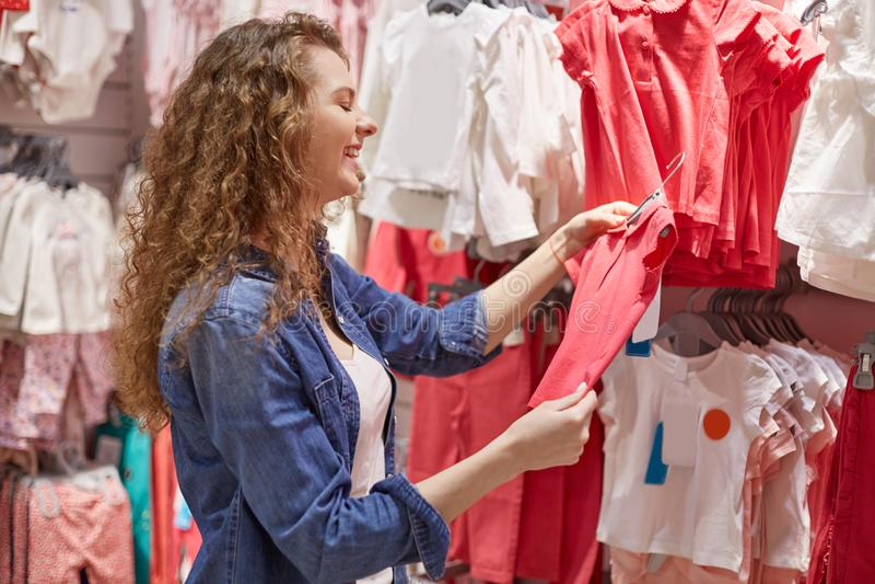A jovem mulher entrou o departamento das crianças com roupa para crianças pequenas, sente-o feliz porque tshirt vermelho da serra fotografia de stock